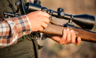 Veteran hands loading a firearm in preparation of a hunt.